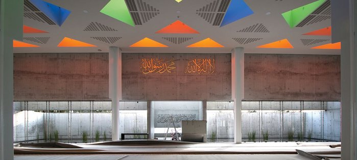 The main concrete wall, orientated to Mecca, with a calming reflective pool creating more subtle reflections on the dramatic ceiling.