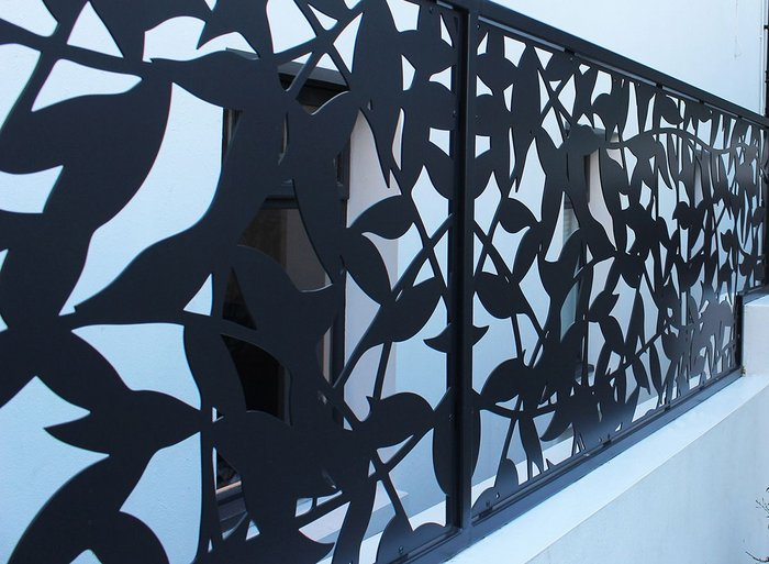 The organic leaf pattern of the privacy screen was designed by the clients then laser cut from a 3mm stainless steel sheet
