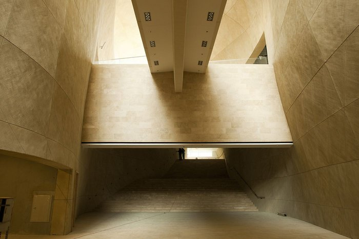 Bulbous curving concrete walls display a changing chiaroscuro of light and shade.