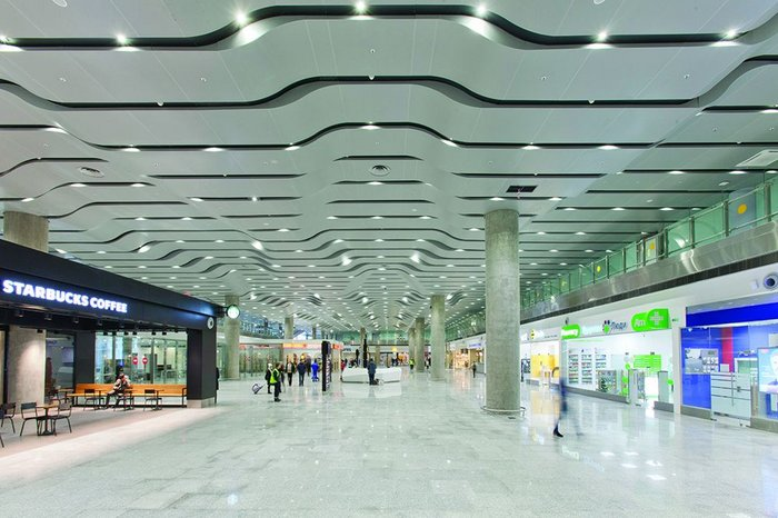 The roof beneath the roof: the arrivals hall has its own very different soffit treatment.
