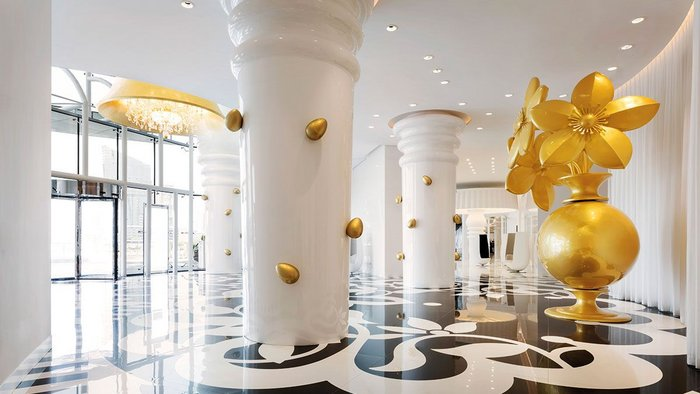 Laser-cut black and white tiles create a supersize pattern for the larger-than-life entrance lobby