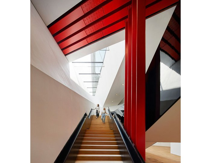The staircase passes below exposed red-painted steels that are holding up the wall of the old museum above.