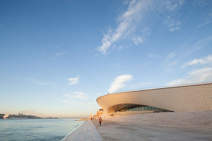 Lisbon's MAAT gallery's riverside elevation, looking west, the 16th century Manuelian style Torre de Belém in the distance. Click image to view