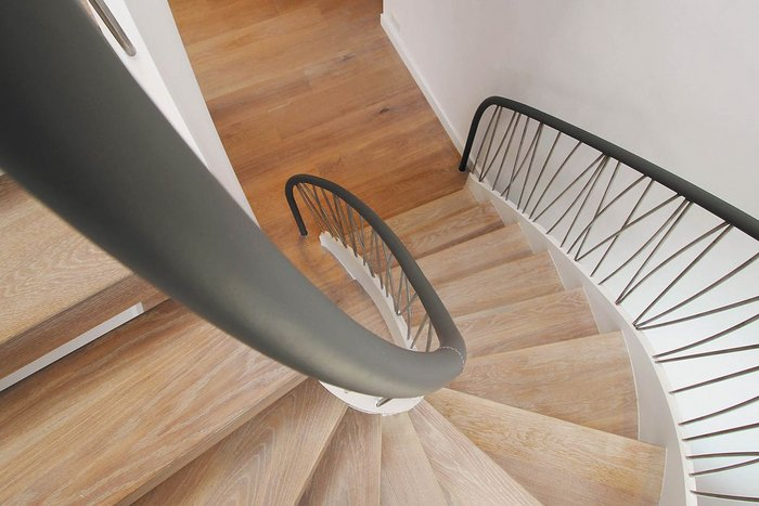 Painted steel staircase with a bespoke stainless steel spindle balustrade and leather handrail.