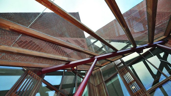 The tectonic plates of the building's facade collide at the focus of the entrance canopy.