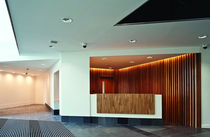 The more intimate, wood-lined reception at the crux of the building before it opens onto the slate and air of the atrium.