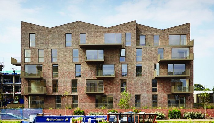 The distinctive roof form of the apartment blocks echoes the historic warehouses that once lined the Grand Union canal here.
