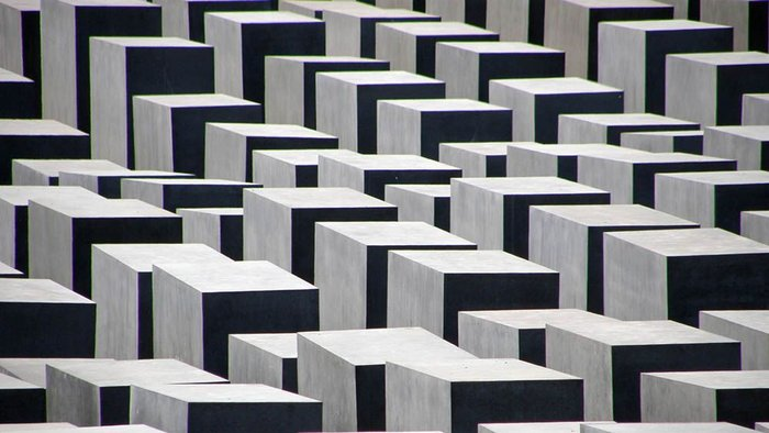 6.	Holocaust Memorial, Berlin, by Peter Eisenman, 2004: another expression of national guilt. Rather than the glowing crystals of Pingusson, this represents the dead by means of 2,711 tomblike solid concrete 'stelae' of varying heights, set in a grid on a nearly five-acre site in the former cleared zone by the Berlin Wall.  A underground centre contains the names of all known Jewish Holocaust victims. The memorial has been controversial in various ways and has needed repairs, but succeeds as an abstract cemetery-like composition. Photo Hugh Pearman.