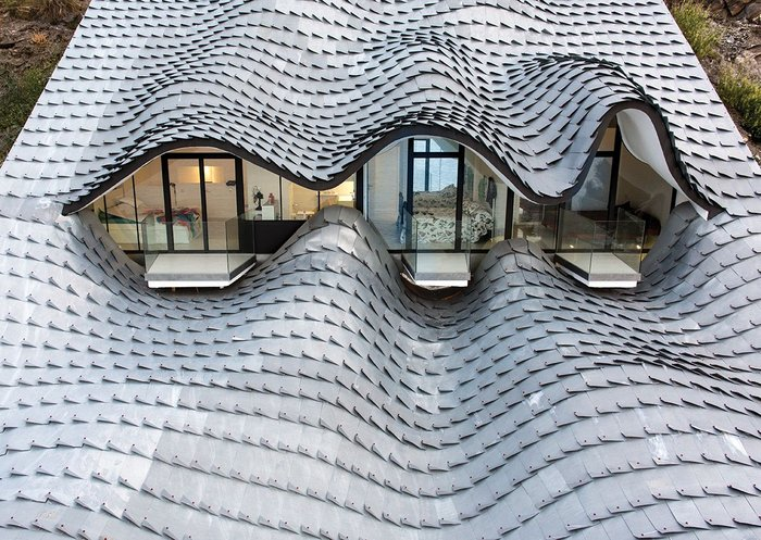 Spain's Casa del Acantilado's zinc shingles adapt to every curve of the building's roof form