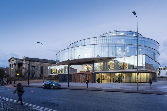 The Blavatnik School of Government viewed at dusk from the main facade onto Walton Street; partially reflecting, partially transparent, a building half dematerialised.