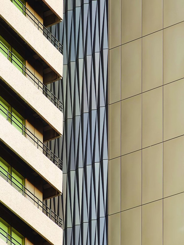 Faceted blue/grey and flat pale umber coloured anodised panels introduce plays of light to a facade that had formerly only absorbed it.