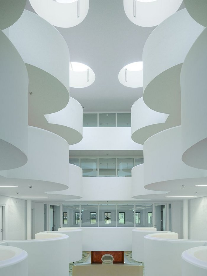 The main hall void, interrupted with semi-circular balconies, references the lost church on the site as well as evoking heavenly clouds parting.