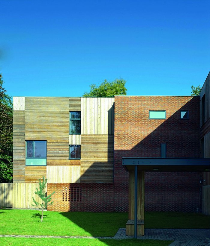 The housemistress' home is timber clad, its front door given a modicum of privacy by a partially perforated brick wall.
