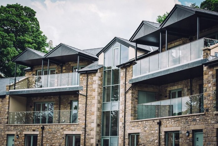 Q-railing balustrades at the Tall Tree Gardens development, Bolton-le-Sands: Glass and stainless-steel balcony railings perfectly match the stone and green surroundings.