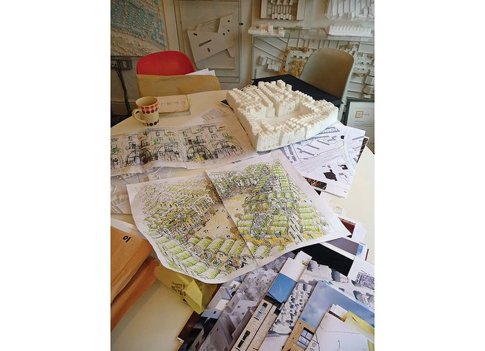 Drawings and models of high density low rise living pile up on Barber's table.