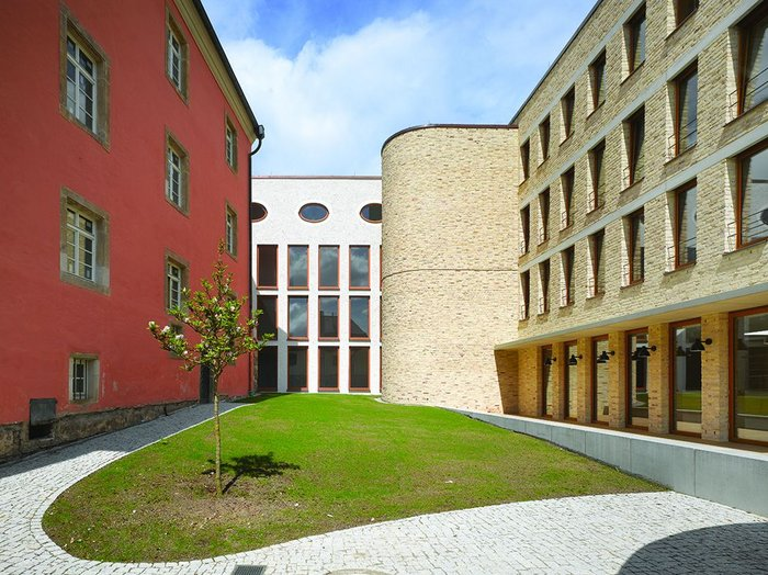 The courtyard to the west of the hall embodies much of the building's juxtaposed aesthetic. Contemporary punched windows facade with concrete lintels meet a modernist stair, a post modern office corridor and the original 17th century facade.