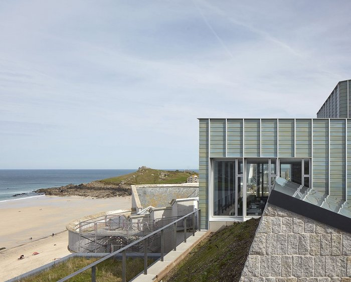 The new upper storey of Tate St Ives has emerged above Porthmeor Beach after a decade of wrangling.