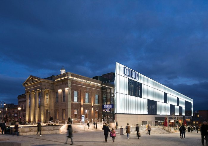 The classical north face of Oldham's Old Town Hall is now contrasted by the bold new west elevation, a light wall with anchor retail set in its rusticated base facing the new Parliament Square.