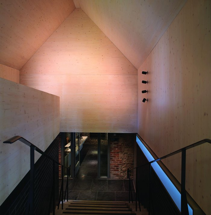 The staircase link building has a plain CLT interior.