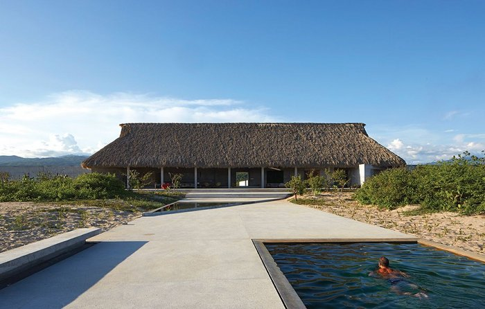Casa Wabi viewed from the beach. It took 18 workers more than two months to weave 40,000 palm tree leaves to construct the roof.