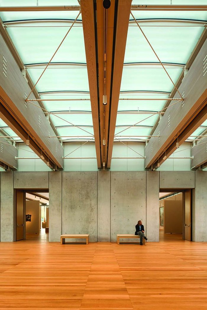 The dual glulam timber beams, spaced 3.5m apart, are spanned by subtle, curved, double-glazed panels and cross-braced. Lighting and sprinklers run discreetly between them.