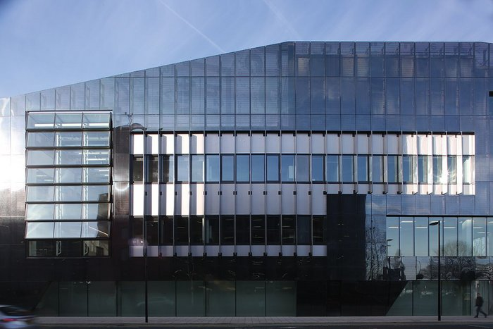 A layered facade incorporates Schueco systems, metallic cladding and a perforated steel veil.