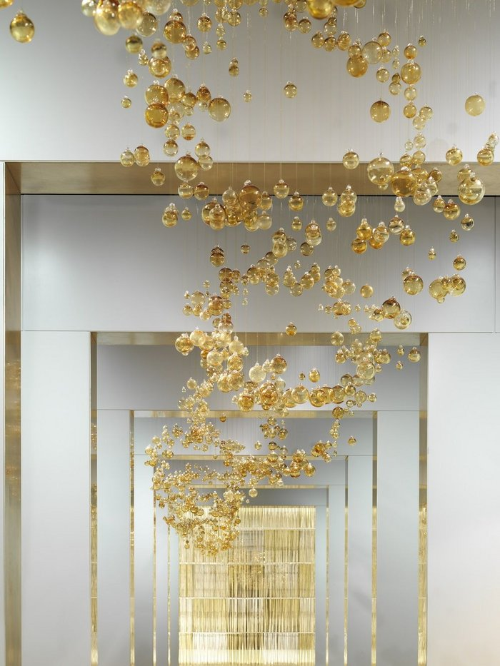 Over 5000 golden baubles have each been hand strung and hung in the art gallery inspired showroom.