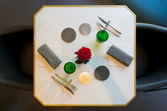 Restaurant tabletop in Neolith Blanco Carrara BC01 with bread plates in Nero Zimbabwe.