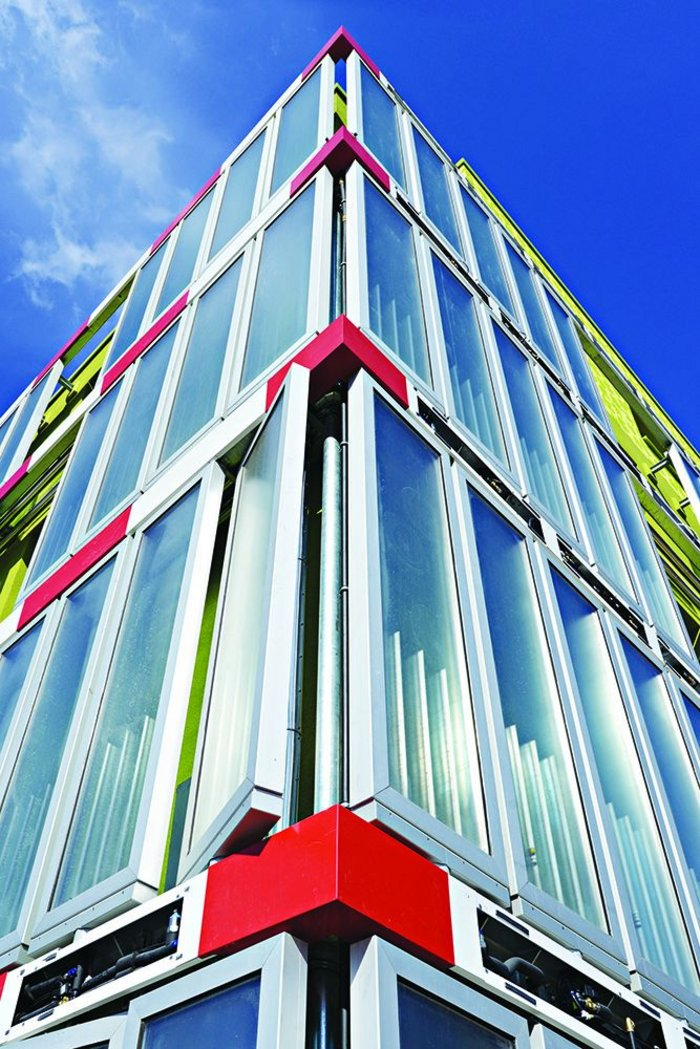 Algae panels, whose biomass pipe runs are hidden behind striking red metal panels, create a distinct look for the BIQ building.