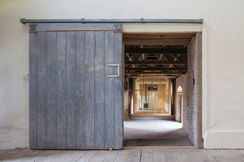 Inside the barn looking south, the gallery seeming to hover within the grade II listed space.