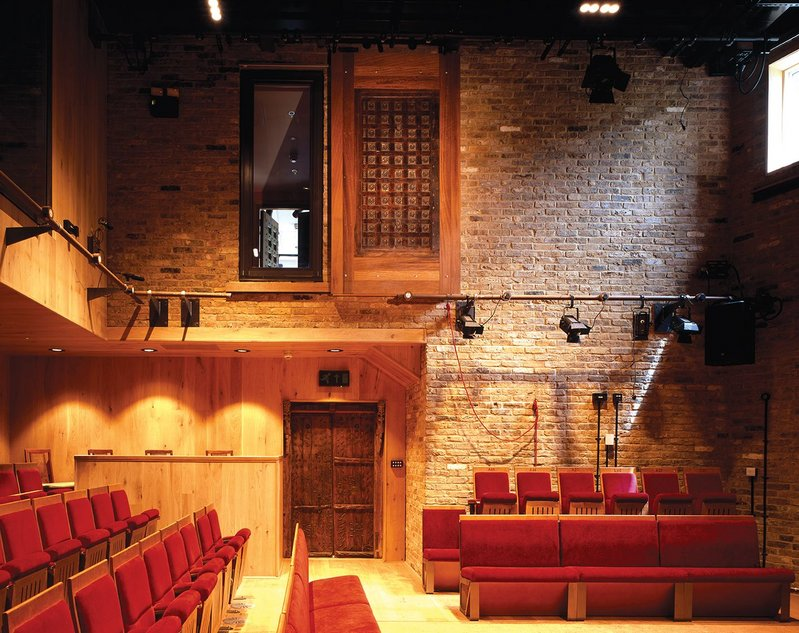 Visitors enter through ornate Indian double doors into an unexpected cosy theatre of exposed brick, oak panelling, red seats, natural light and a rammed earth stage.