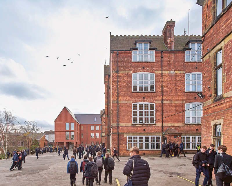 The school yard now has a visual end-stop in the form of the new building with its entrance arcade. Original 1880s buildings in the foreground.