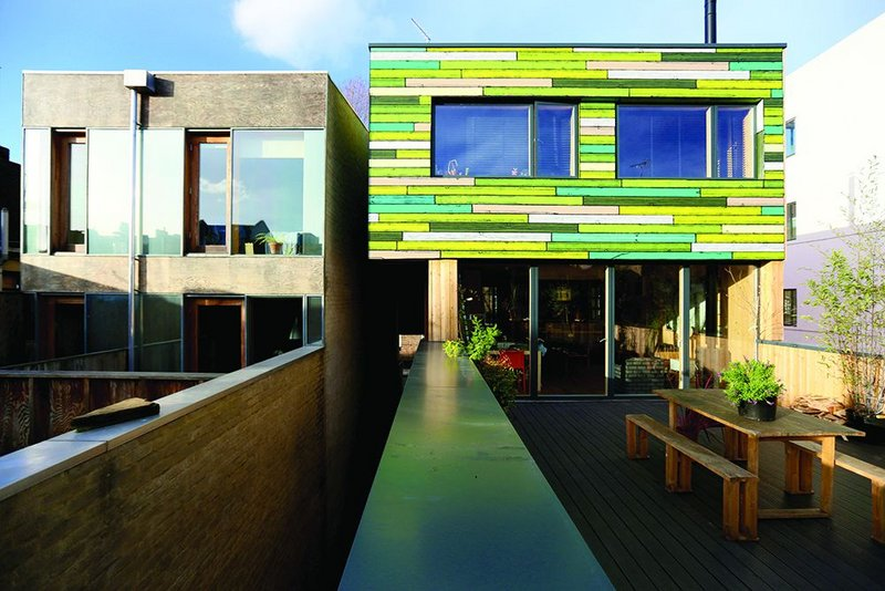 Rear elevation, with second storey clad in Woods' colourful timber panelling, and first floor external terrace.