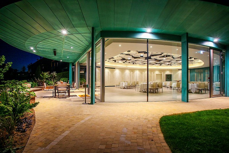 A ring beam portal frame cantilevers over the entrance, its soffit clad in the characteristic KME Tecu Patina.