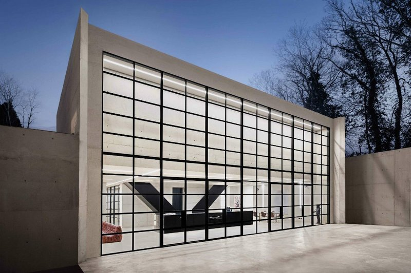 The rear elevation with its concrete and black framed glazed wall that spans the width of the building.
