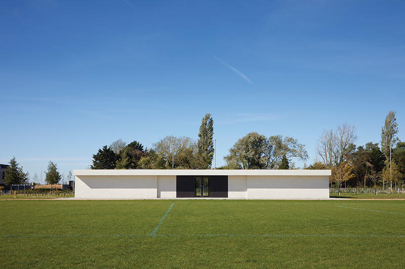 The sports pavilion sits on the edge of a large playing field with four changing rooms and eight WCs. Its facade is pushed and pulled to make it welcoming.
