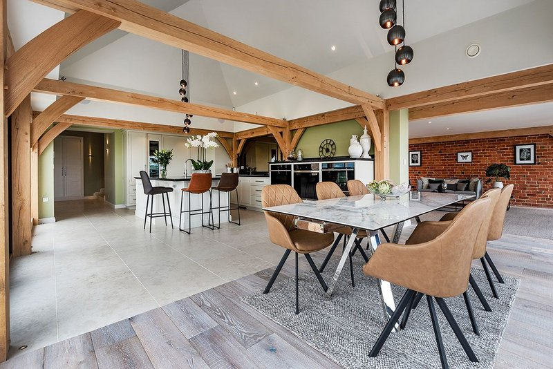 Oak flooring creates a contrast with the porcelain floor tiles that run throughout the open-plan living area.