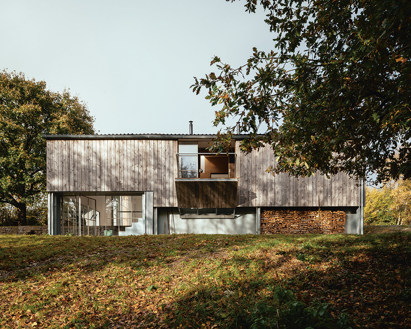 A folding balcony overlooks woodland that drops into the valley to the south of the building.