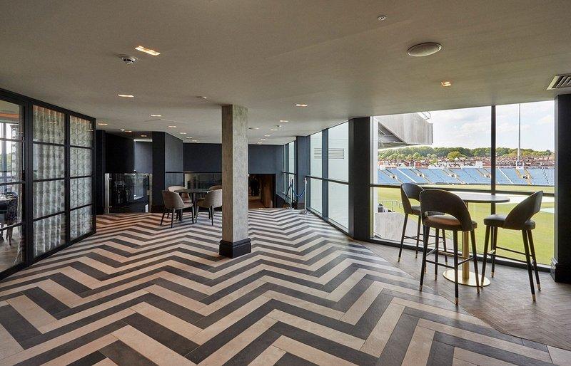 Technicolour timber-effect tiles create a character herringbone floor at Emerald Headingley Stadium.