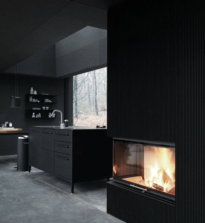 Looking towards the fireplace and kitchen area – everything forms part of a singular, branded design aesthetic.