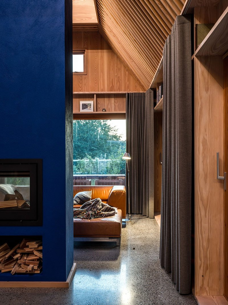 The Yves Klein blue chimney rises through the centre of the house, dividing the living space from the kitchen.