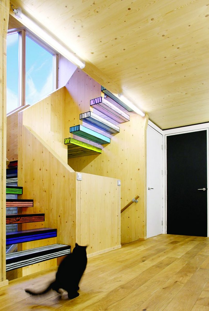 The staircase projects out from the side elevation to meet the wider second storey, providing cover over the side alley and more bedroom space.