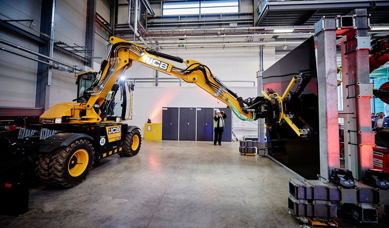 A JCB with a modified end effector places a panel into a frame, demonstrating a semi-automated technique that could be applied in construction