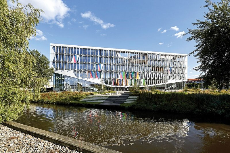 Overlooking a nearby river, the south face of the Kolding campus makes full use of its dynamic facade of triangulated panels.