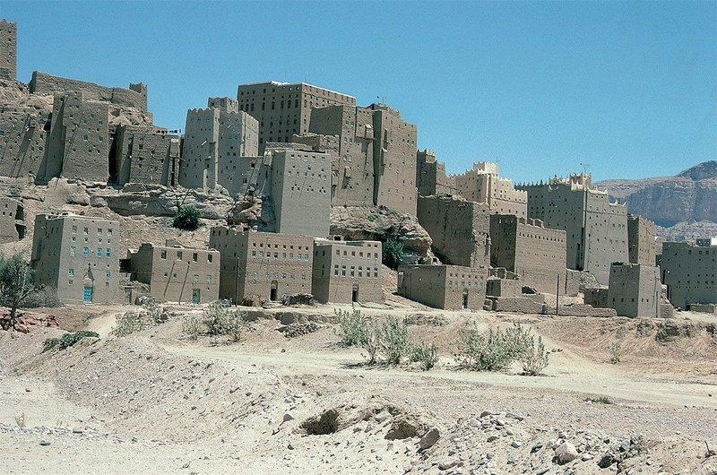 A tight cluster of mud brick towers and more recent houses along the wadi (ravine) banks in the town of Habban.