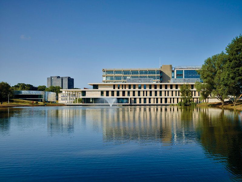 The new Silberrad Student Centre sits between the lake and the library  – the library extension is on the right.