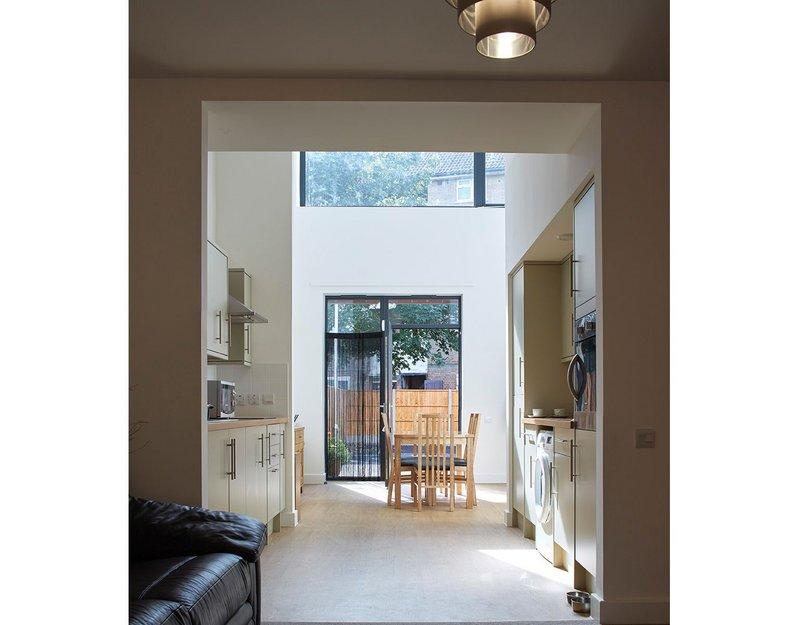 Inside a light-filled living space, the front door with galley kitchen at the centre.