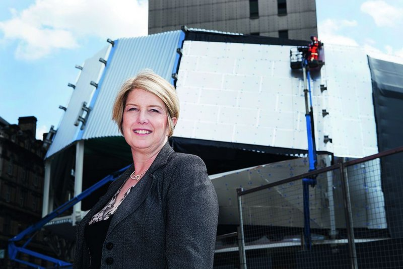 Carol Stitchman stands in front of the main entrance of the new New Street Station. Behind, the cladding framework that will support the building's stainless steel ribbon facade.