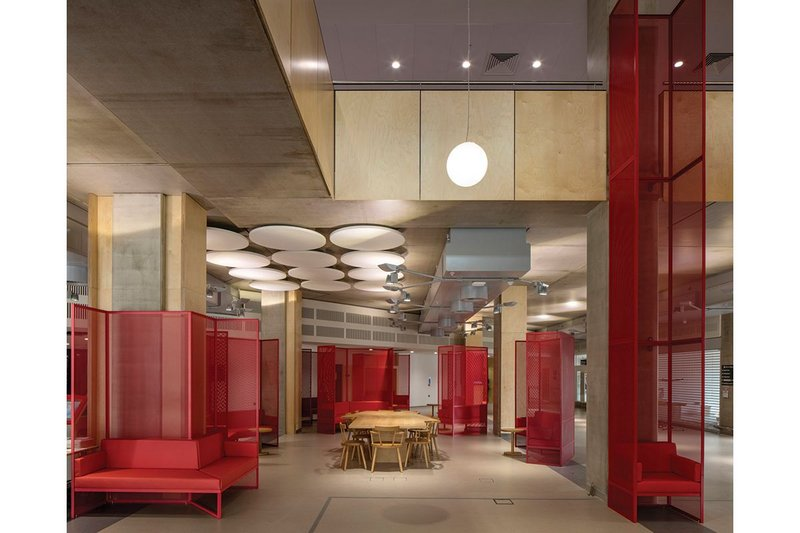 Birch ply and red steel furniture form  part of the palette of materials for the Care Village atrium.