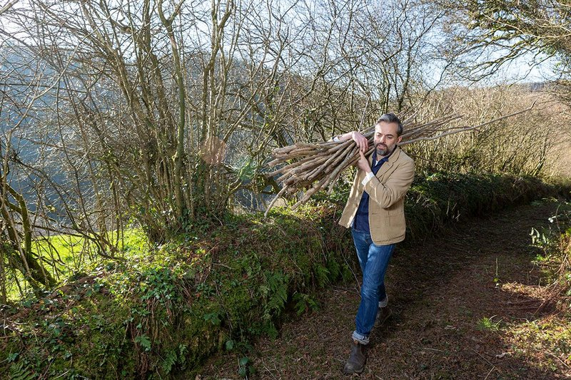 Niall Maxwell of Rural Office for Architecture at his farm near Carmarthen, shifting a bundle of hazel sticks.